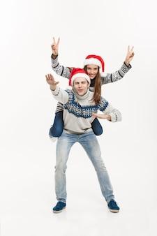 Kerstmisconcept - jong gelukkig paar in sweaters die op de rug van rit genieten die op witte grijze muur wordt geïsoleerd.