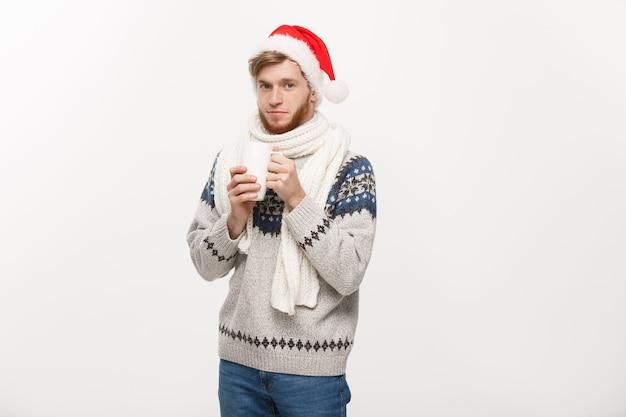 Kerstmisconcept - jonge baardmens in sweater en santahoed die een hete koffiekop houden die op wit met exemplaarruimte wordt geïsoleerd.