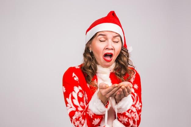 Kerstmisconcept - kerstmanvrouw die op witte muur niezen.