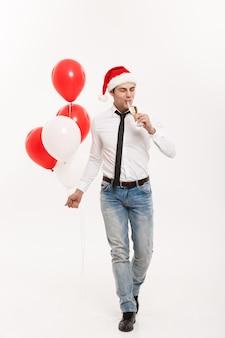 Kerstmisconcept - knappe gelukkige zakenman die met rode ballon lopen viert de vrolijke kerstmuts van de kerstmisslijtage.