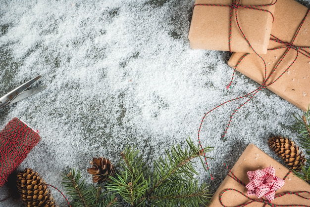 Kerstmisconcept, lijstachtergrond met sneeuw, kerstboomtakken, giften of cadeaus, denneappels en decoratie