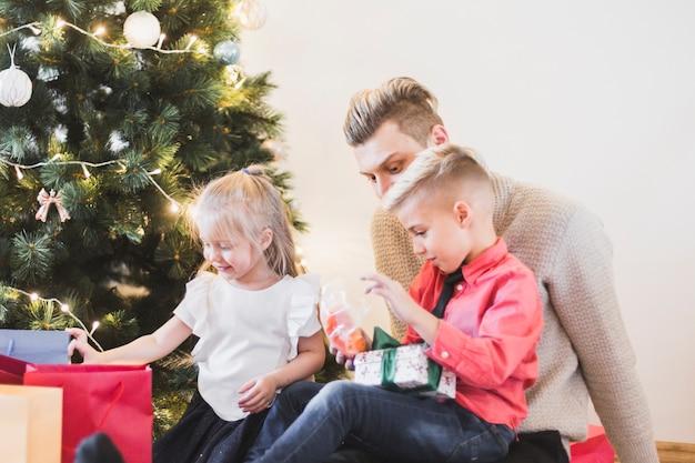 Kerstmisconcept met familiezitting naast kerstmisboom