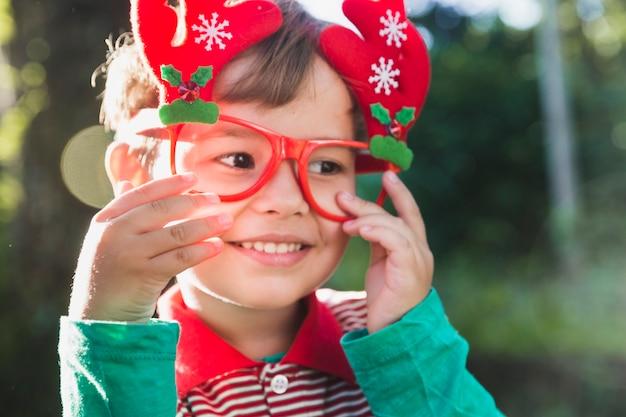 Kerstmisconcept met jong geitje dat glazen draagt