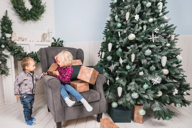 Kerstmisconcept met jonge geitjes op laag naast kerstmisboom