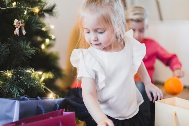 Kerstmisconcept met meisje die cadeaus bekijken
