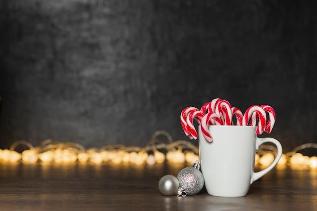 Kerstmisconcept met mok met suikergoed en bollen