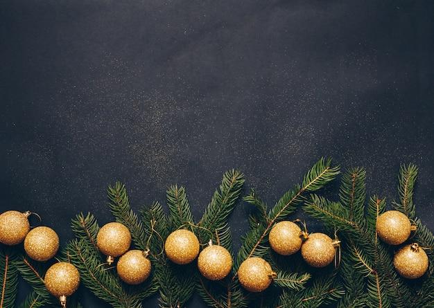 Kerstmisconcept op een zwarte achtergrond met speelgoed en groene spar.