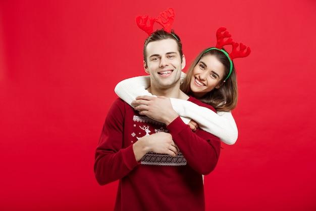 Kerstmisconcept - romantisch paar in kerstmissweaters die elkaar koesteren.