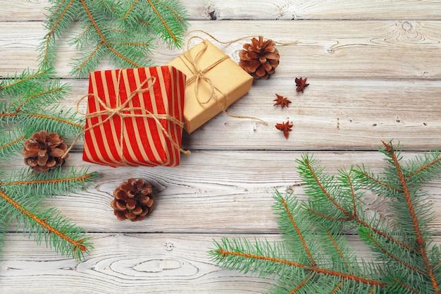 Kerstmisdecoratie, giftdoos en takken van de pijnboomboom op houten achtergrond