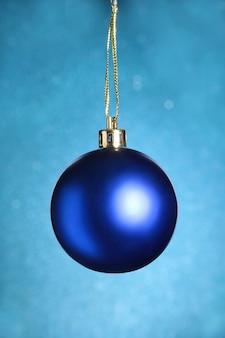 Kerstmisdecoratie met blauwe bal op blauwe achtergrond met sneeuwvlokken die van hemel vallen. fijne feestdagen samenstelling.