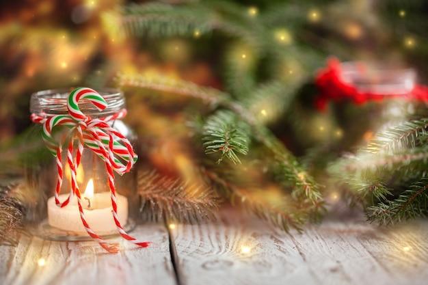 Kerstmisdecoratie met kaarsen in kruik op vakantieachtergrond.