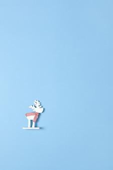 Kerstmisdecoratie, stuk speelgoed witte herten in geruite sjaal op pastelkleur blauwe achtergrond met copyspace. feestelijk, nieuwjaar.