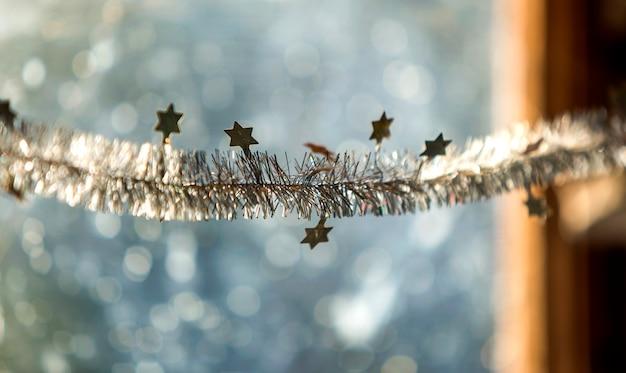 Kerstmisdecoratie van het close-updetail, zilveren sterren en regen op vage vensterlicht bokeh