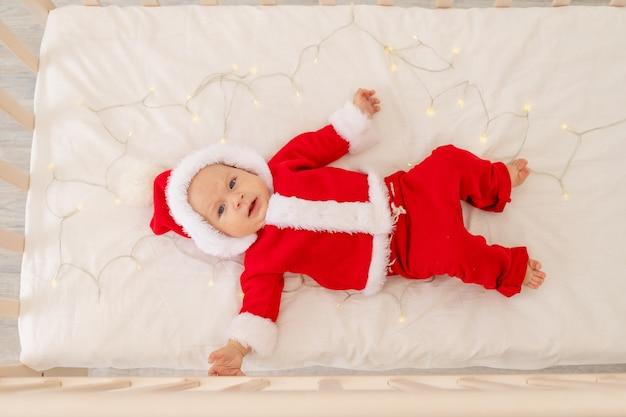 Kerstmisfoto van een baby in een kerstmankostuum die in een wieg thuis liggen