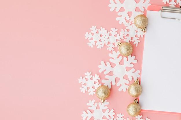 Kerstmisgift in de handen van vrouwen en notitieboekje op een roze achtergrond, een mening van hierboven