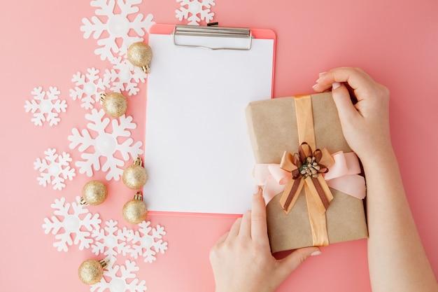 Kerstmisgift in de handen van vrouwen en notitieboekje op een roze, een mening van hierboven