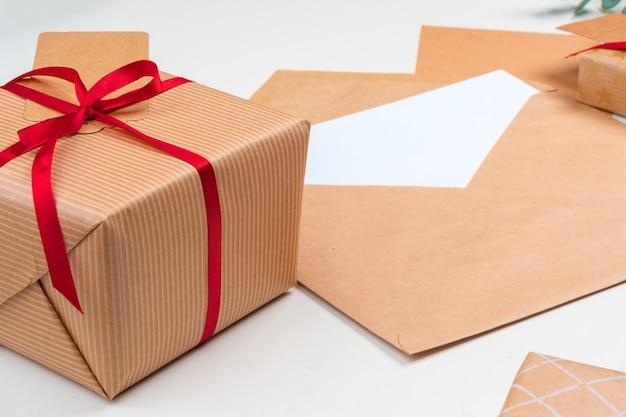 Kerstmisgift met rode boog en groetkaart op witte houten achtergrond