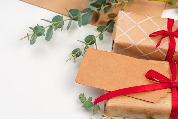 Kerstmisgift met rode boog en groetkaart op witte houten