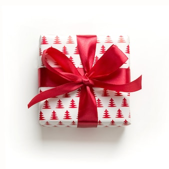 Kerstmisgift met rode boog op wit. kerstmis. gelukkig. nieuwjaar. vlakke stijl.