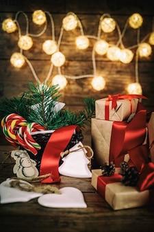 Kerstmisgiften met dozen, naald, mand, suikergoedrietkegels op houten achtergrond