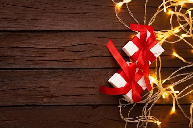 Kerstmisgiften op een oude geweven houten achtergrond met gloeilampen