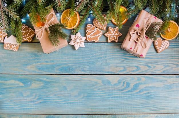 Kerstmisgiften op een witte houten achtergrond met boomtakken.