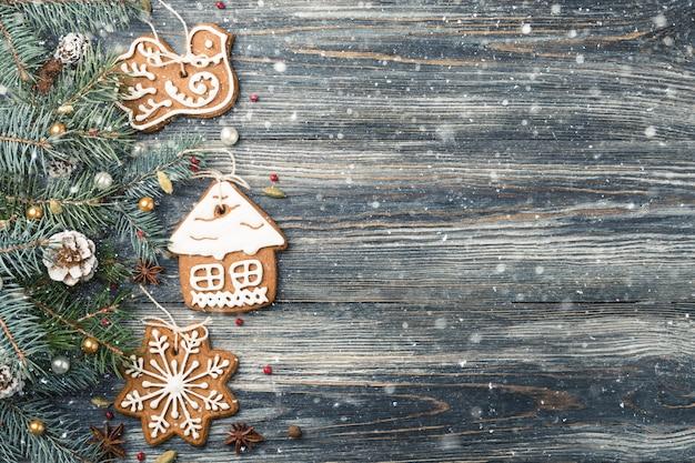 Kerstmisgrens van peperkoekkoekjes op sparren over sneeuw houten achtergrond, exemplaarruimte.