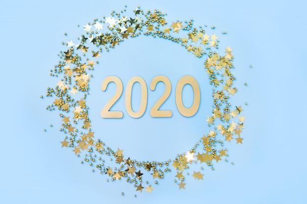 Kerstmiskader met datum nieuw 2020 jaar en gouden confettiensterren op blauw. plat leggen. uitzicht van boven. xmas verticale rand.