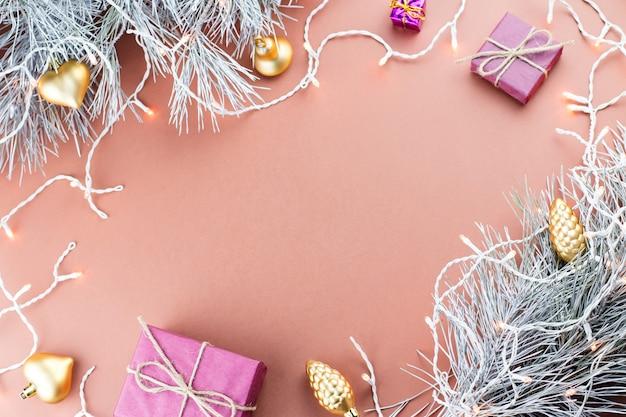 Kerstmiskader met kerstmislichten, sparrentakken en ornamenten op bruine achtergrond