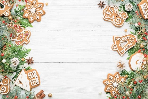 Kerstmiskader met ornamenten en peperkoekkoekjes op witte houten achtergrond.
