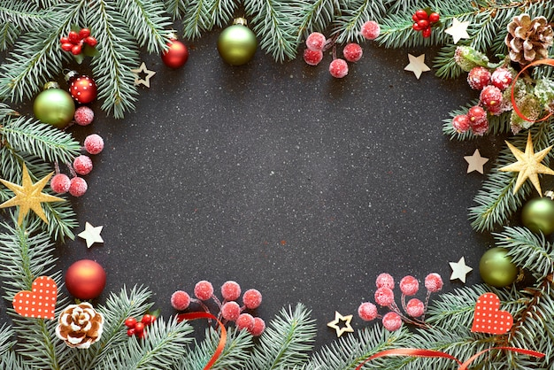 Kerstmiskader met spartakjes, bessen, snuisterijen en linten in rood en groen,