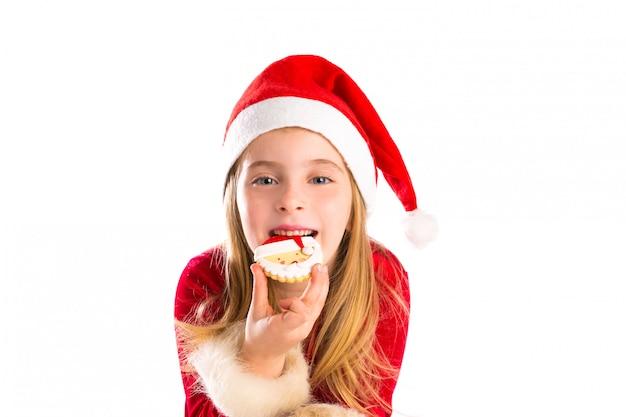 Kerstmiskerstman die koekje en meisje van het kerstmis het blonde jonge geitje eten