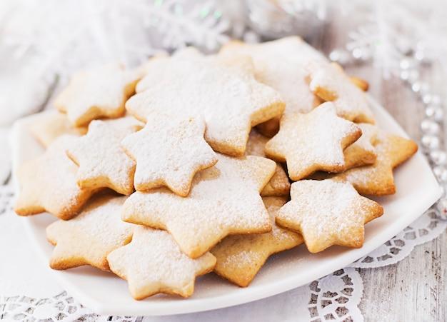 Kerstmiskoekjes en klatergoud op een houten lijst
