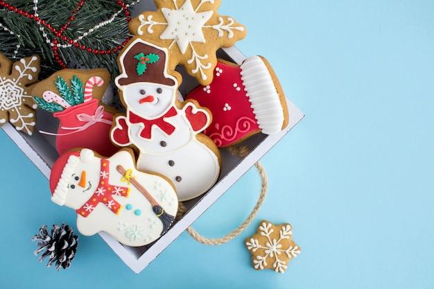 Kerstmiskoekjes in het witte houten dienblad op de blauwe oppervlakte. bovenaanzicht. kopieer ruimte.