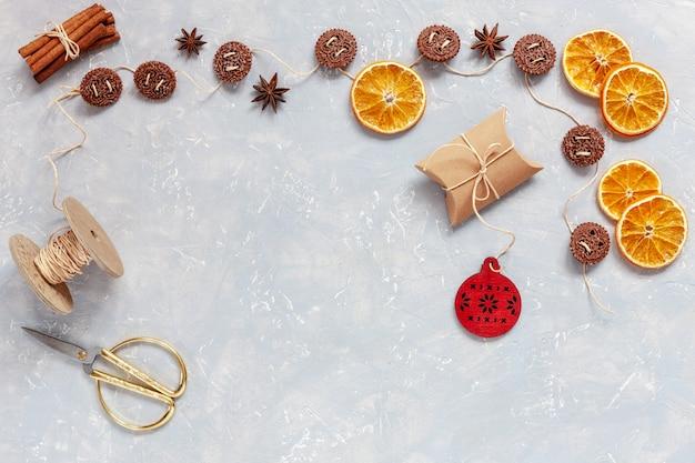 Kerstmiskoekjes, kruiden, droge oranje plakken op grijze concrete achtergrond