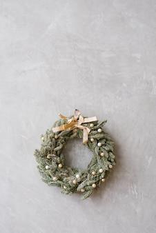 Kerstmiskroon met beige schaal op grijze muur, exemplaarruimte