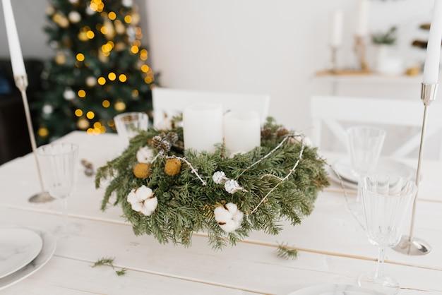 Kerstmiskroon met witte kaarsen op de feestelijke lijst