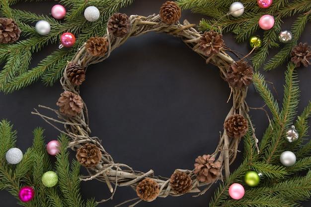 Kerstmiskroon, sparrentakken, kleurrijke glasballen op zwarte achtergrond.