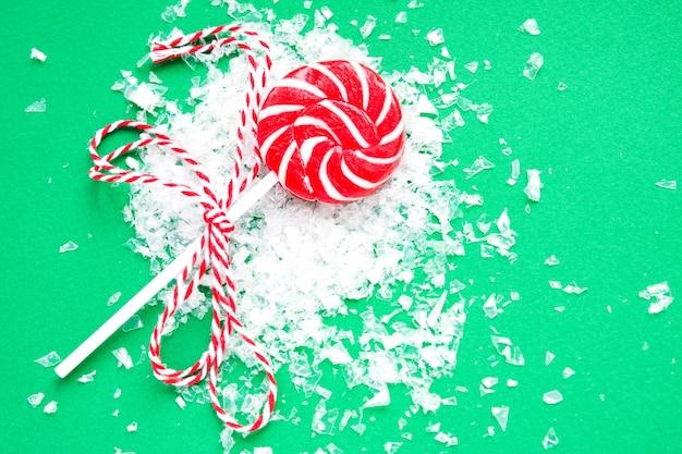 Kerstmislolly en sneeuw op groen. plat leggen. nieuwjaar en kerstsnoepjes