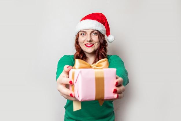 Kerstmismeisje in santahoed met doos op grijs wordt geïsoleerd die.