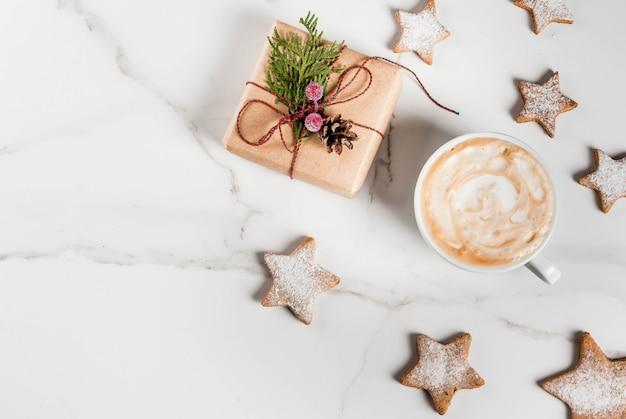 Kerstmisontbijt, koffiemok met de koekjes van de peperkoekster, met kerstmisgift of heden, op de witte houten mening van de lijstbovenkant copyspace