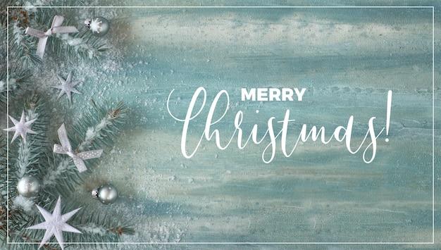 Kerstmisoppervlakte met spartakjes, zilveren snuisterijen en sterren op groene munt abstracte oppervlakte. panoramische compositie, spandoekontwerp met frame en tekst