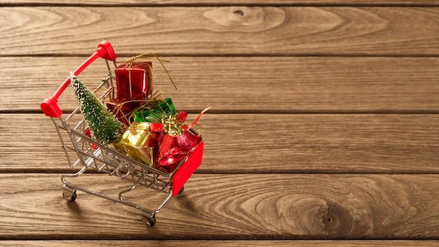 Kerstmisornamenten op miniatuurboodschappenwagentje over het hout voor webbanner