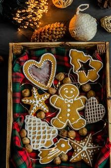 Kerstmispeperkoek met witte die suikerglazuursuiker op een donkere achtergrond wordt geschilderd.