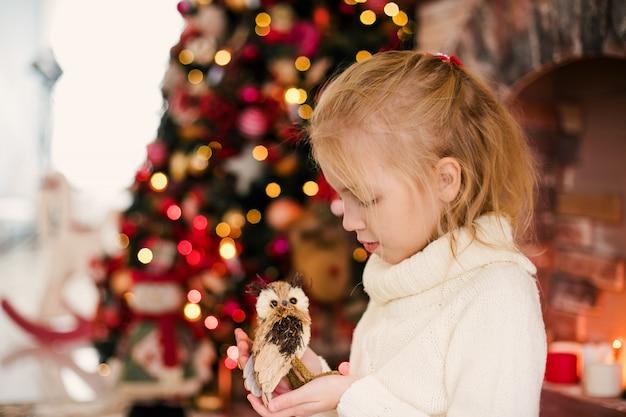 Kerstmisportret van het gelukkige meisje van het blondekind in witte sweater die stuk speelgoed uil houden