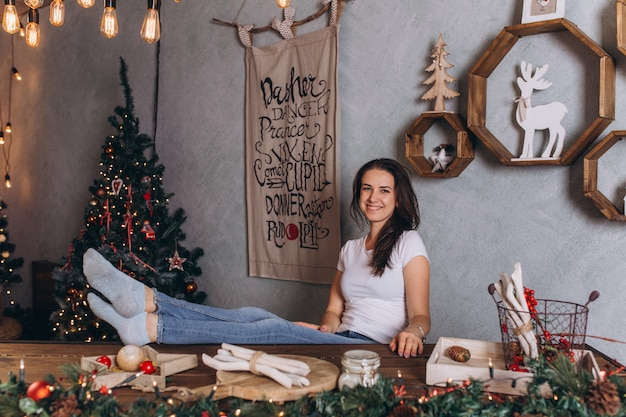 Kerstmisportret van jonge vrij donkerbruine vrouw bij gezellig huis