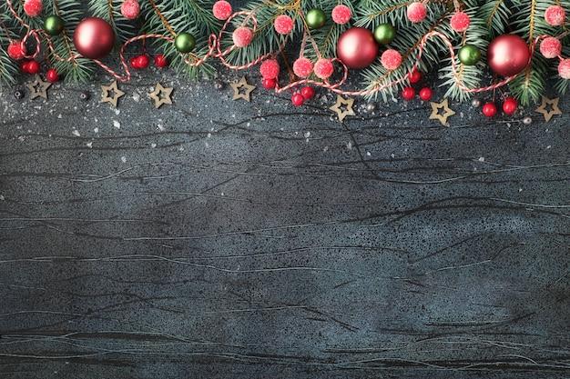 Kerstmisregeling met spartakjes, rode en groene snuisterijen en lichten op donkere, tekstruimte