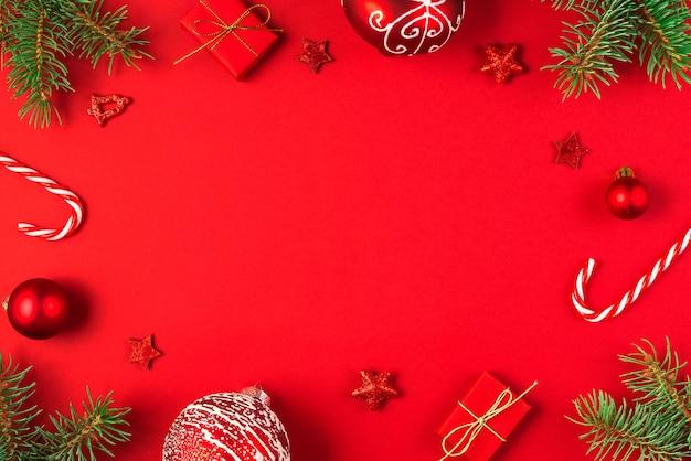 Kerstmissamenstelling gemaakt van dennentakken, geschenkdozen, decoraties voor de feestdagen en snoep op rode achtergrond