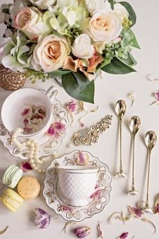 Kerstmissamenstelling met bloemen en witte theekoppen