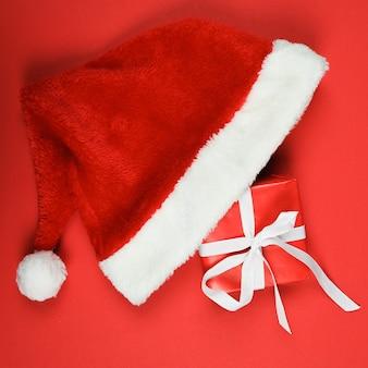 Kerstmissamenstelling met de kerstmuts van de giftdoos op rode achtergrond